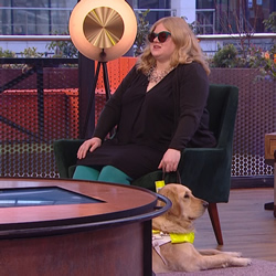 Amy in a TV studio with Guide Dog Ava at her feet.