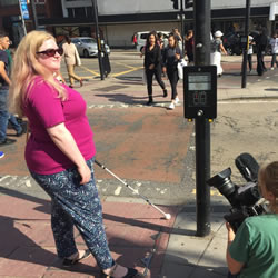 Amy with her cane at a crossing being filmed by a camera to our right